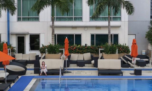 Ein Frau chillt am Pool des Novotels Manila und tippt in ihrem Handy