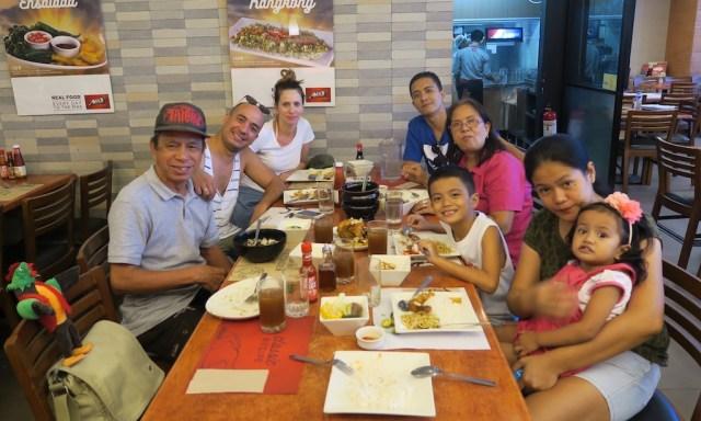 Eine große Familie sitzt am Tisch im Max Restaurant in Angono