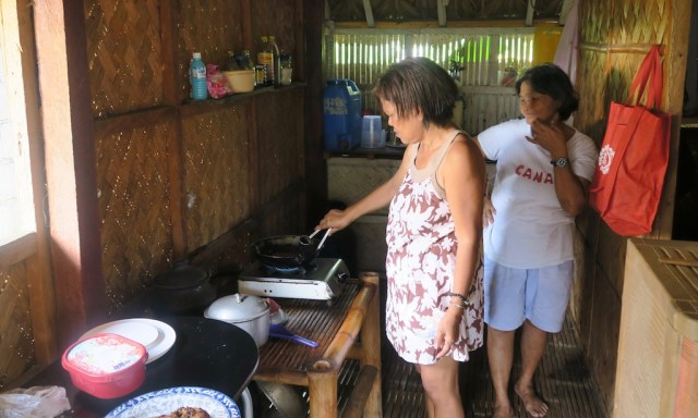 Ein Frau in der Küche brät Fisch