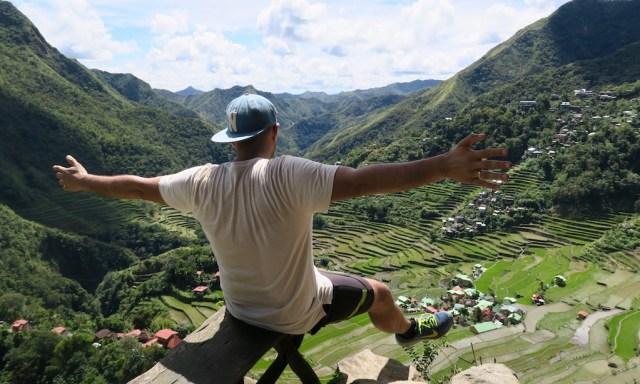 Ein Mann streckt Beine und Arme raus und blickt in das Tal von Batad