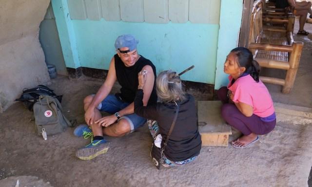 Apo Whang-Od tätowiert einen Touristen auf dem Boden sitzend