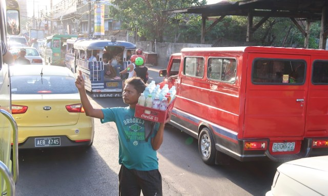 Ein philippinischer Wasserverkäufer verläuft Wasser an Bus auf eine vielbefahrenen Straße in Cebu City