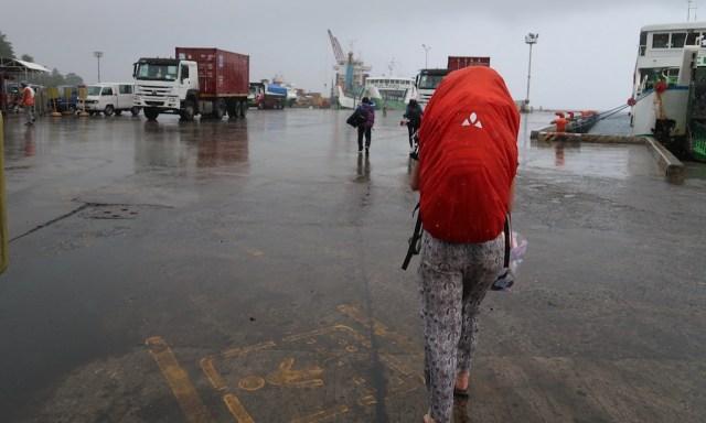 Die Maus mit einem großen trekkingrucksack mit roten Überzug im verregneten Dumaguette geht zur Fähre von Montenegro Liner