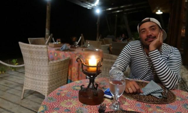 Bendja sitzt abends entspannt am Tisch des Sunset-Restaurants des Coco Grove Resorts