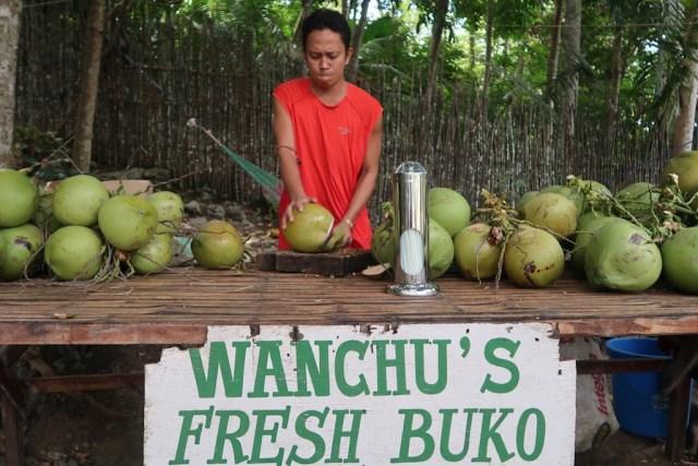Ein Mann zerhackt eine Buko an seinem Buko-Juice-Stand