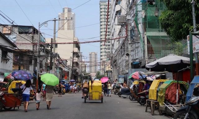 Bunte Sonnenschirme, gelbes Trycicle in den Straßen von Malate