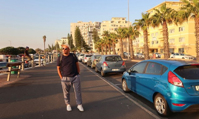 Bendja tankt Abendsonne auf der Seapoint Promenade in Kapstadt