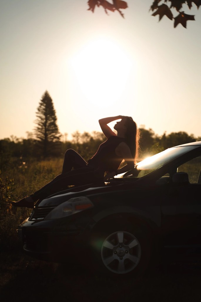 beautiful golden hour photo of Natalia holding her head in the morning light while sitting on the hood of her Nissan Versa