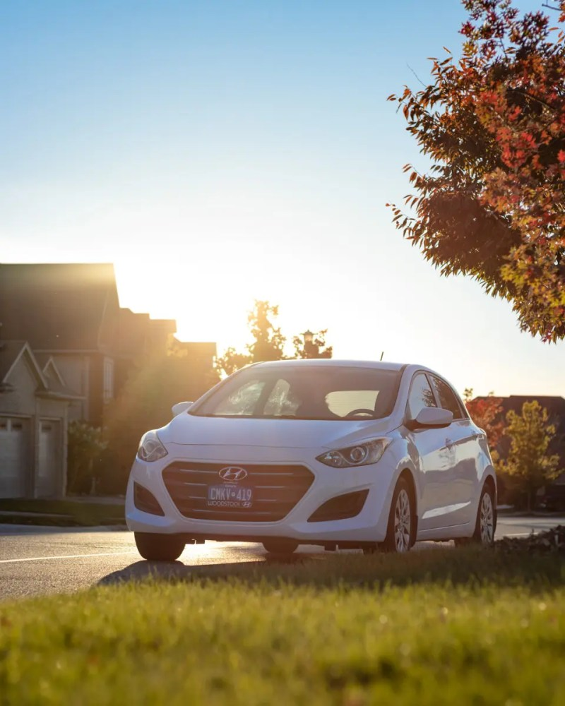 Our white 2016 Hyundai Elantra GT in the sunset with glowing grass in the foreground
