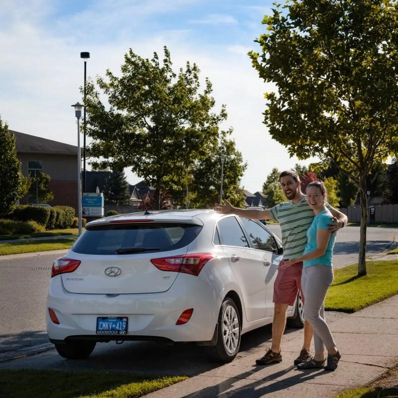 Ben and Natalia stand next to their new white 2016 Hyundai Elantra GT hatchback car