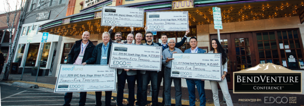 2019 winners with checks outside of Liberty Theater