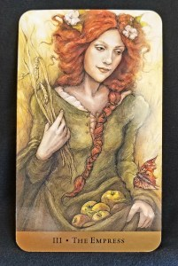 Woman with red hair holding a basket of apples in her lap and wheat in her hand.