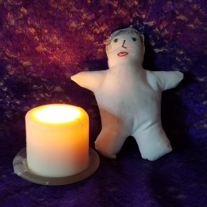 Poppet next to a candle
