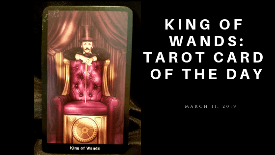 King of Wands - Man standing behind a red chair, resting on the back