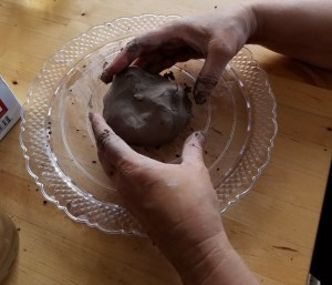 Money Drawing Talismans - mixing herbs into clay by hand