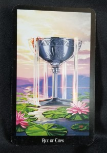 Ace of Cups - a silver chalice floating on a pomd with lily pads, water flowing from it