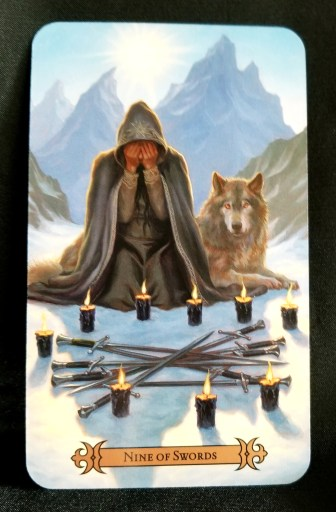 Nine of Swords - a kneeling man covering his face with his hands, nine crossed swords on the ground in front of him