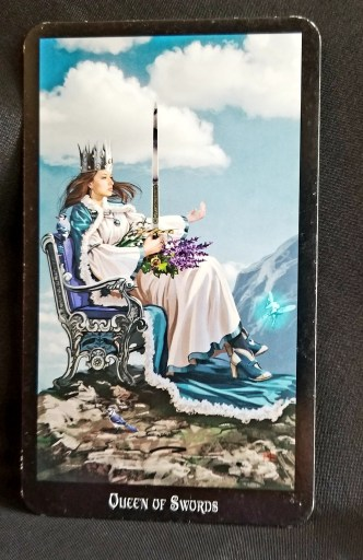 Queen of Swords Tarot - A queen seated on a throne on a cliff, a tiny fairy in front of her