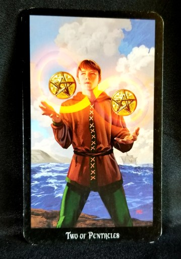 Two of Pentacles - Tarot Card: A young man juggling two pentacles