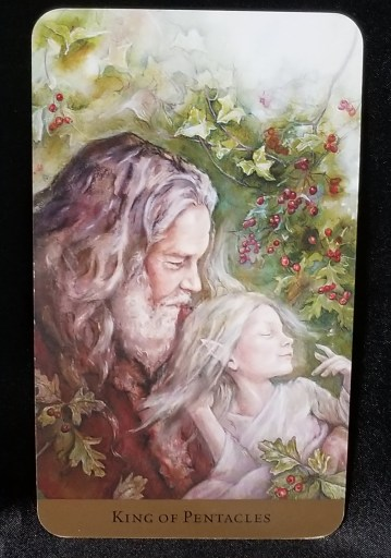 King of Pentacles - Tarot Card: An older gentleman in red robes holding a young elfin child