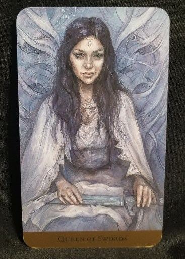 Queen of Swords Tarot Card - A calm, serene looking woman sitting with a sword in her lap