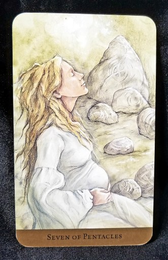 Seven of Pentacles Tarot Card:  A very pregnant woman sitting amidst carved rocks, looking content
