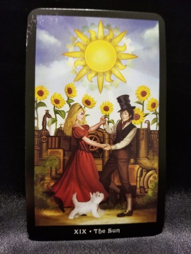 The Sun - Tarot Card:  A man and a woman holding hands under the sun- surrounded by sunflowers