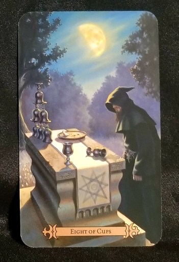 Eight of Cups - Tarot Card:  A monk or priest at an altar with eight silver cups upon it.  A crescent moon hangs overhead.