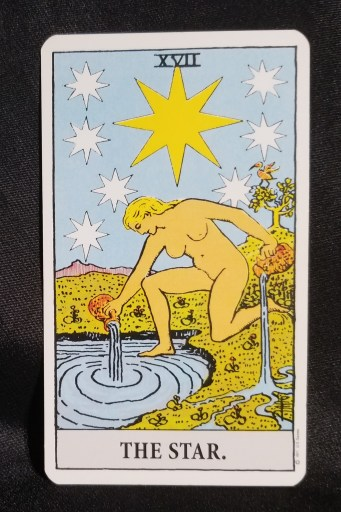 The Star - Tarot Card:  A woman is pouring water from two pitchers, one into a pond, the other onto land.  A seven pointed star is over her head.