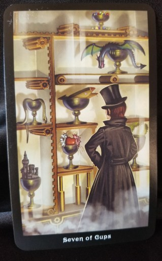 Seven of Cups - Tarot Card:  A man dressed in a top hat and long coat stands in front of a case filled with various items.  He appears to be trying to make a choice.