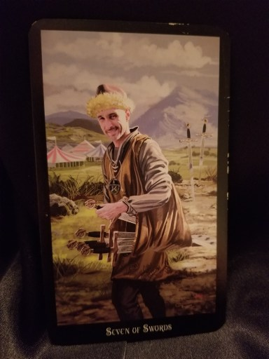 Seven of Swords- A standing in front of several tents, He is carrying five sowrds with two behind him.