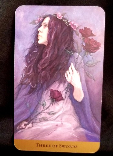Three of Swords - Tarot Card:  A Young woman looks whistfully into the future. She holds three thorny, red roses.