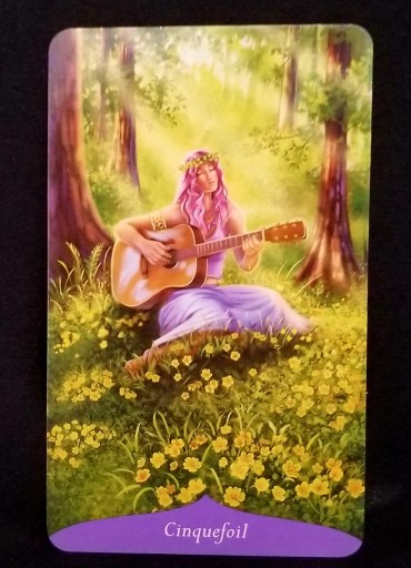 Cinquefoil - A beautiful woman is seated in a forest.  She is playing a guitar and appears to be singing to the cinquefoil flowers all around her.