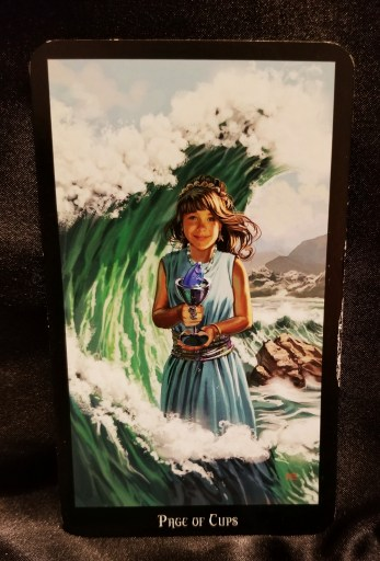 Pape of Cups - Tarot Card:  A young girl standing in the ocean, a wave curling above her head. She holds a chalice containing a fish.