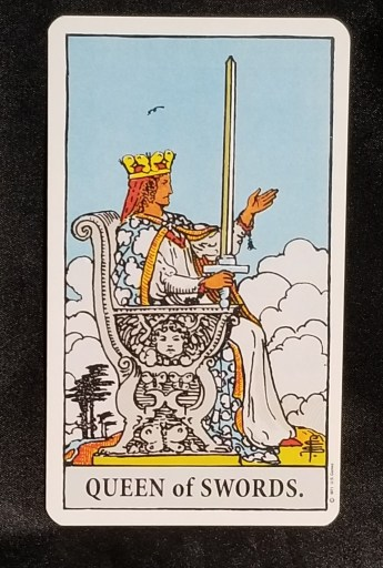 Queen of Swords - Tarot Card:  A regal queen sitting an a throne. Her left hand is raised and she is holding a sword in her right.