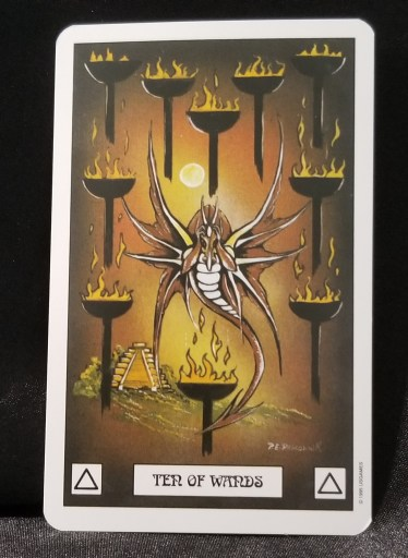 Ten of Wands - Tarot Card:  A brown dagon holding his head in his hands. He is surrounded by then flaming torches.