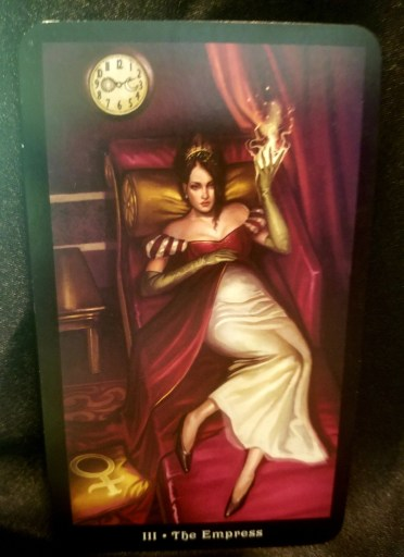The Empress - Tarot Card:  A woman reclining on a red couch, soft flames extending from her left hand.