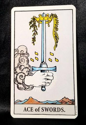 """Ace of Swords - Tarot Card""""  A hand holding a sword encircled by a crown is piecrcing through a grey cloud."""