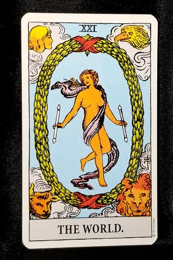 The World - Tarot Card: A nude woman holding two wands.  She is surrounded by a laurel wreath.