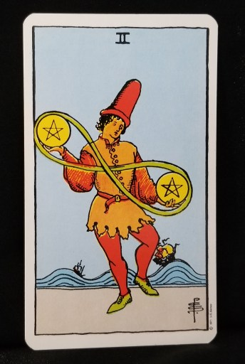 Two of Pentacles - Tarot Card:  A jester juglling two pentacles.  Their travels makes an infinity loop.