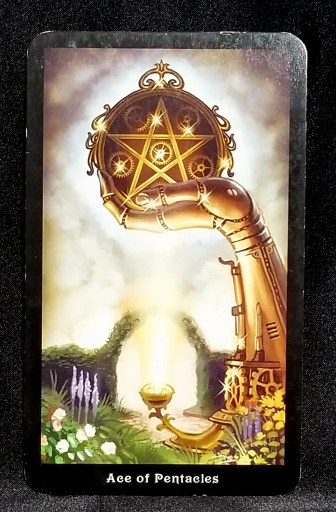 Ace of Pentacles - A mechanical hand holding aloft a large brass pentacle.