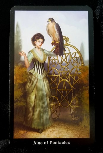Nine of Pentacles- A woman dressed in Steampunk attire holding a hawk on her arm.  An old-fashioned bicycle with 9 pentacles as spokes is beside her.
