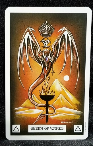 Queen of Wands - A red dragon with a crown over her head,hoving over a flaming torch.