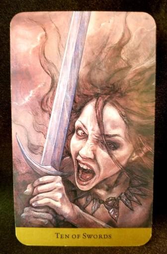 Ten of Swords- A ciolent looking woman holding a sword screams at you.