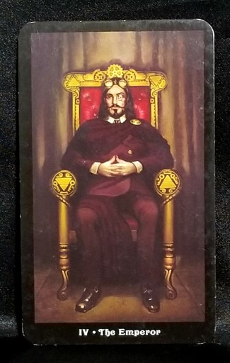The Emperor : A regal looking man wearing a steam punk helmet seated upon a throne.