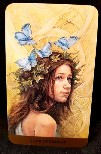 Four of Swords- a young girl, her head encircled by blue butterflies. looks out into space.
