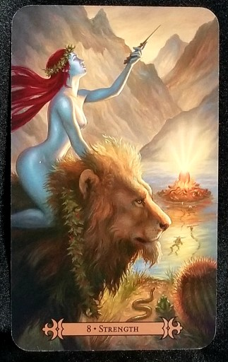Strength - A red-haired woman riding upon a lion.