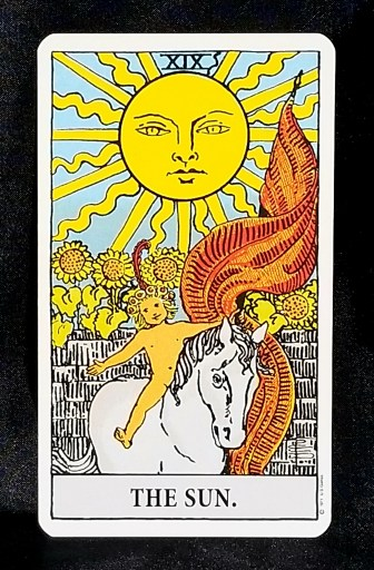 The Sun- A small child astride a white horse, a glorious sun overhead