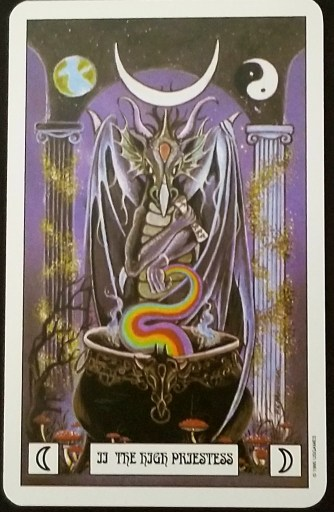 The High Priestess- A grey dragoin standing over a cauldron.  One hand holds a rainbow. the other a scroll.