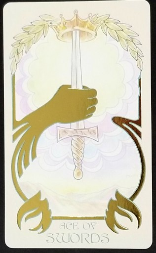 Ace of Swords- A golden gauntleted hand holding a sword upright.